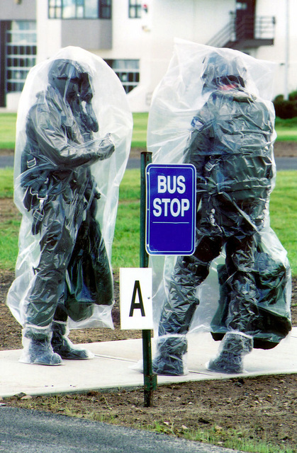 """Two Pilots from the from the 174th Tactical Fighter Wing, New York Air National Guard, Syracuse, N.Y. wear protective plastic body bags during chemical warfare training, part of an Operational Readiness Inspection (ORI) held on the base. The pilots are waiting at crew bus stop """"A"""" for their bus"""