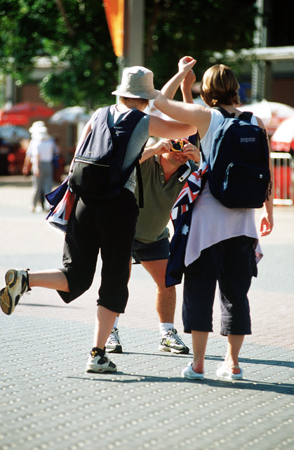 A group of tourists to the Olympic Park pose for the camera mimicking as though they are holding the Olympic torch at the Sydney 2000 Olympics. Numerous US Department of Defense personnel (Not shown) are taking part in the Olympics, from coaches and support staff to athletes competing in various venues