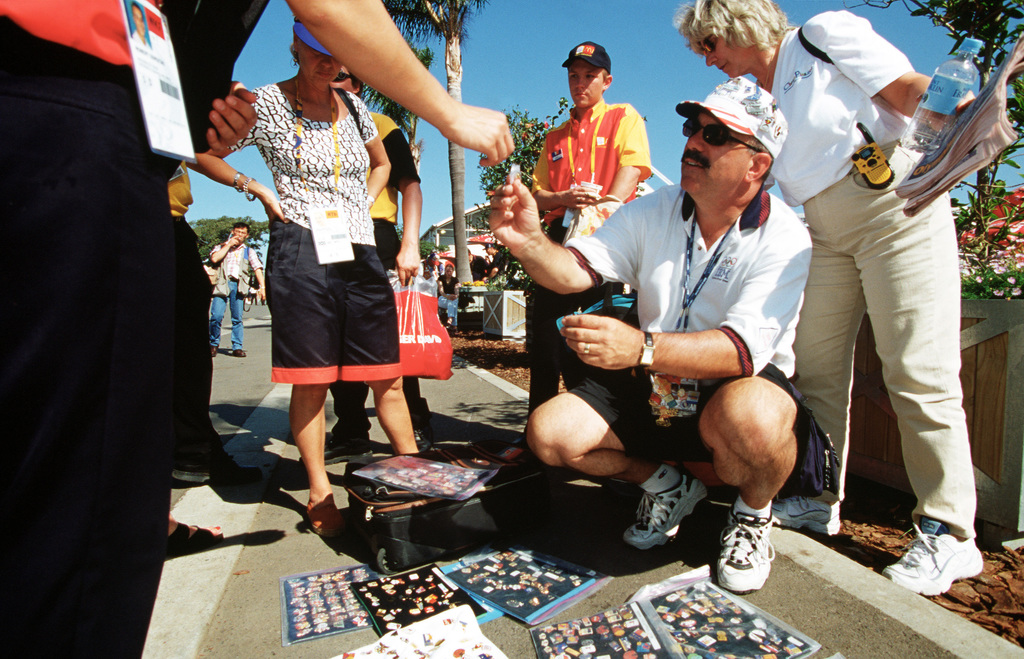 American Bob McKeon, of Poway, California (Kneeling), said the Sydney Olympics is his seventh. McKeon, an avid pin trader and collector, says he brought 20,000 of his 100,000 pin collection to trade with during the sydney 2000 Olympics. Numerous US Department of Defense personnel (Not shown) are taking part in the Olympics, from coaches and support staff to athletes competing in various venues