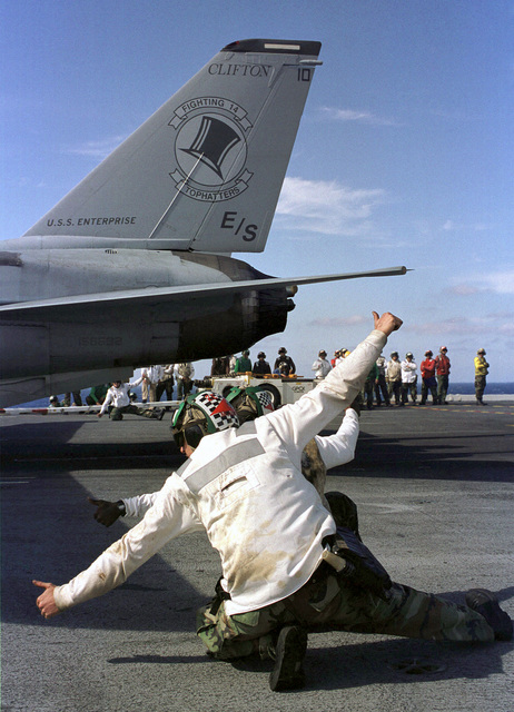 """Two US Navy (USN) catapult final checkers give the all clear signal before launching a USN F-14 Tomcat aircraft from Fighter Squadron One Four (VF-14) """"Tophatters"""", during flight operations aboard the aircraft carrier USS ENTERPRISE (CVN 65)"""