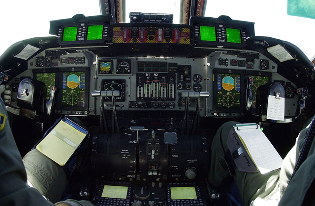 "An overview of new ""Glass Cockpit"" technologies on a C-141C Starlifter aircraft from the 89th Airlift Squadron (USAFR), Wright-Patterson Air Force Base, Ohio. More than sixty aircraft in the current C-141 fleet will undergo major modification. Each will receive the All Weather Flight Control System (AWFCS) consisting of a digital autopilot, advanced avionics display, and Ground Collision Avoidance System (GCAS). Other major improvements include a Defensive Systems (DS), Fuel Quantity Indicating System, and GPS modifications. The display units seen in front of each pilot are the Display Avionics Maintenance Unit (two green screens on top), Display Units (two large color screens in front ..."