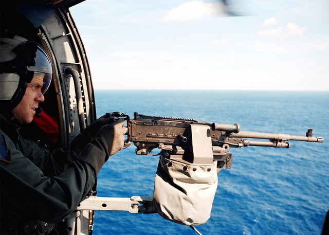 "Aviation Anti-Submarine Warfare Operator First Class (AW1) Ron Jankowski from Toledo, Ohio, fires an M-60 machine gun from the door of an SH-60F ""Seahawk"" helicopter attached to the ""Tridents"" of Helicopter Anti-Submarine Squadron Three (HS-3)"