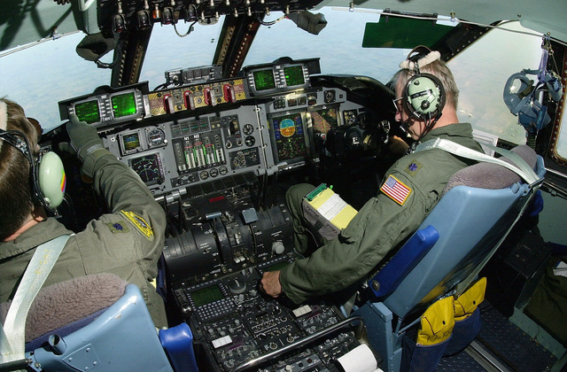 "(left to right) US Air Force Lieutenant Colonel ""Hawkeye"" Pierce and USAF Lieutenant Colonel Chuck Hanks, pilots, fly a Project Trans-Am mission in a C-141C Starlifter aircraft, which features new ""Glass Cockpit"" technologies during a landing approach. The aircraft and crew are assigned to the 89th Airlift Squadron (USAFR), Wright-Patterson Air Force Base, Ohio. More than sixty aircraft in the current C-141 fleet will undergo major modification, each will receive the All Weather Flight Control System (AWFCS) consisting of a digital autopilot, advanced avionics display, and Ground Collision Avoidance System (GCAS). Other major improvements include a Defensive Systems (DS), Fuel Quantity ..."