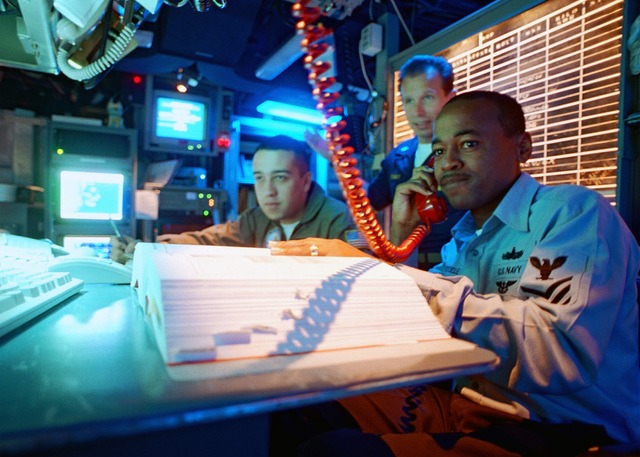 Sonar Technician Second Class (ST2) Wendell Steele from Philadelphia, Pennsylvania, Air Warfare SPECIALIST AIRMAN (AWSAN) Jose Vacio from El Paso, Texas and AWSAN Jeffery Bonay from Brunswick, Maine, communicate with Commander Destroyer Squadron One Eight (COMDESRON 18) while standing watch aboard USS ENTERPRISE (CVN 65)