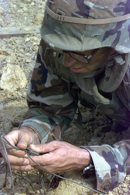 SPECIALIST John Ake rigs a fuse to an M1A1 Bangalore torpedo during the 326th (Sapper Eagle) Engineer Battalion's live-fire exercise at Fort Campbell, Kentucky