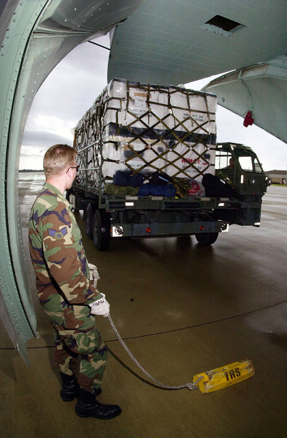 US Air Force Technical Sergeant Kenneth Holmes drives a 25K loader to the cargo ramp of a C-141C Starlifter aircraft, while USAF SENIOR AIRMAN Michael Waye watches clearances on the opposite side. As part of Project Trans-Am, this U.S. Air Force Reserve aerial port team moved $100,000 dollars worth of excess war reserve medical supplies onto a C-141C of the 89th Airlift Squadron, Wright-Patterson Air Force Base, Ohio. The pallets of supplies were flown from Shaw Air Force Base, North Carolina, to Grissom Air Reserve Force, Indiana. Due to resizing, surplus medical supplies were donated to native North American-Indian communities. They will identify what they need from an inventory list...