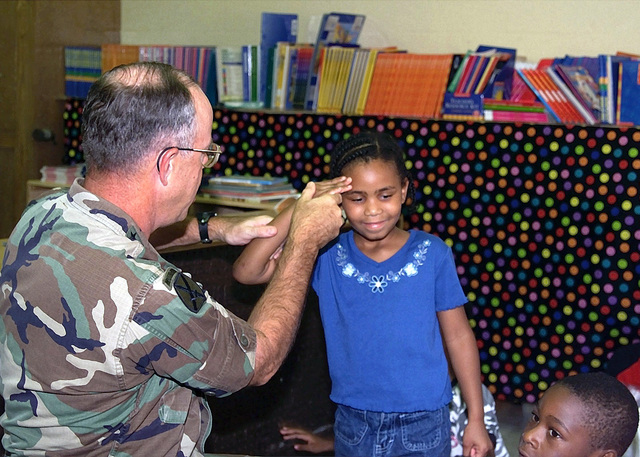Lieutenant General (LTG) Lawson W. MacGruder III, Deputy Commanding General, Forces Command and CHIEF of STAFF, teaches one of the students at Arkwright elementary school how to render a proper military salute. LTG MacGruder visited the class and read a book. Forces Command (FORSCOM) sponsors the school in the Partners In Education program. The program provides leadership in the formation and growth of effective partnerships that ensure success for all students