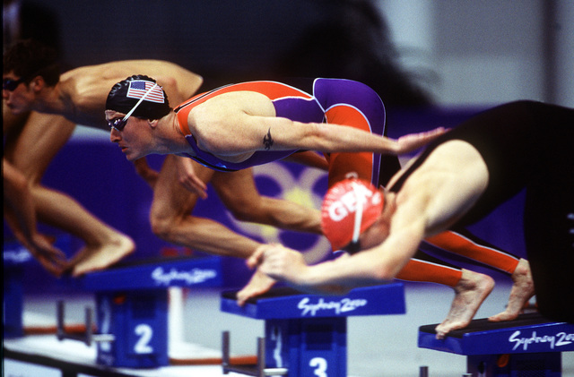 Right side profile, medium shot of US Army SPECIALIST Chad SENIOR (Middle, in black cap) as he dives off the starting block at the swimming venue during the Modern Pentathlon at the Olympic Park on Saturday September 30th, 2000. SPC SENIOR comes to the 2000 Sydney Olympic games by way of the US Army's World Class Athlete Program