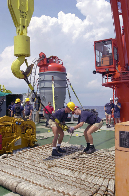 "Members of the United States Navy's Deep Submergence Unit (USNDSU) crane, tend a ""bumper pad"" to be craned in preparation for the deployment of a Submarine Rescue Chamber (SRC) (in the background), during Exercise PACIFIC REACH 2000"