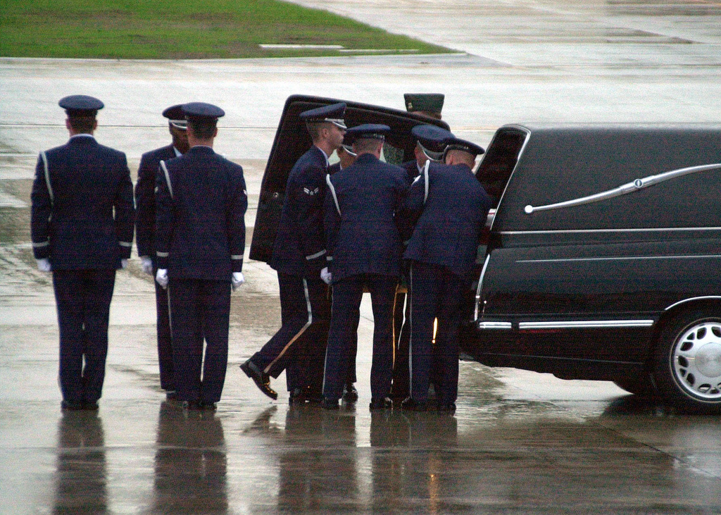 Members of the US Air Force 86th Air Wing Honor Guard prepare to load the caskets of fallen sailors from USS COLE (DDG 67), into a hearse, at Ramstein Air Base, Germany, on October 13, 2000. The sailors were caught in the explosion during the bombing of Cole in the Yemen port city of Aden