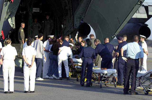 Disembarking from a United States Air Force (USAF) C-141 Starlifter from Germany, medical staff transport injured Sailor's from the Arleigh Burke class guided missile destroyer USS COLE (DDG 67) to the Portsmouth Naval Hospital
