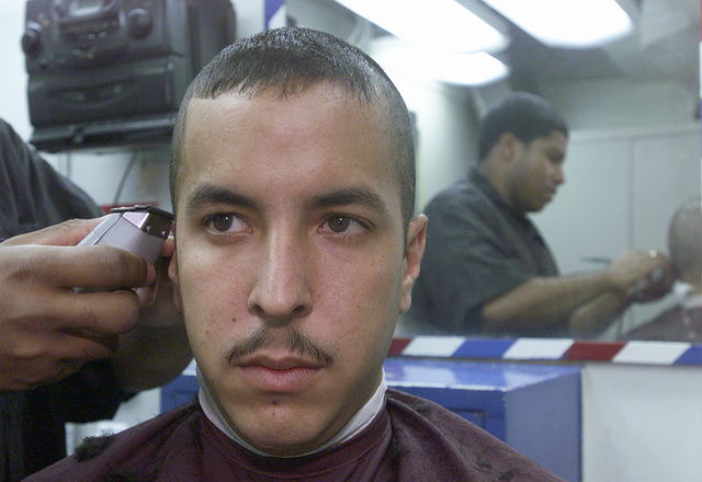 """Aviation Anti-submarine Warfare Operator 3rd Class (WO3) Hector Rubles from Fajardo, Puerto Rico, receives a """"High and Tight"""" haircut in the ship's barber shop aboard the USS DEYO (DD 989)"""