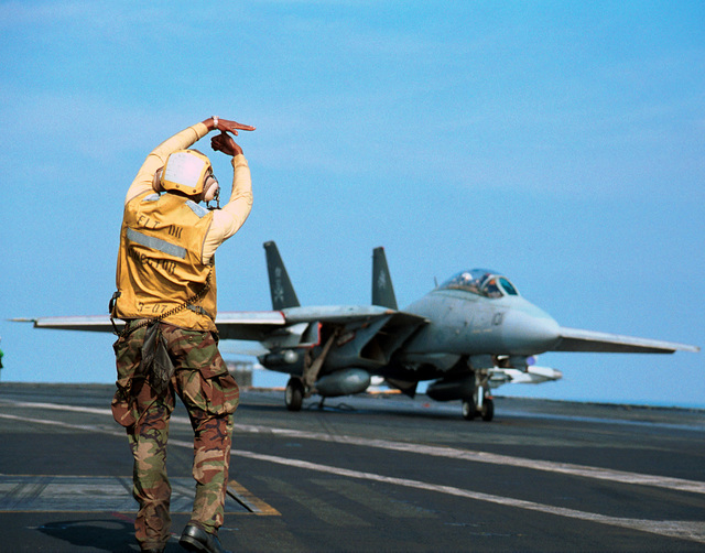"Aviation Boatswain's Mate 3rd Class Edmond Scott directs an F-14 ""Tomcat"" attached to the ""Jolly Rogers"" of Fighter Squadron One Zero Three (VF-103) aboard USS GEORGE WASHINGTON (CVN 73)"