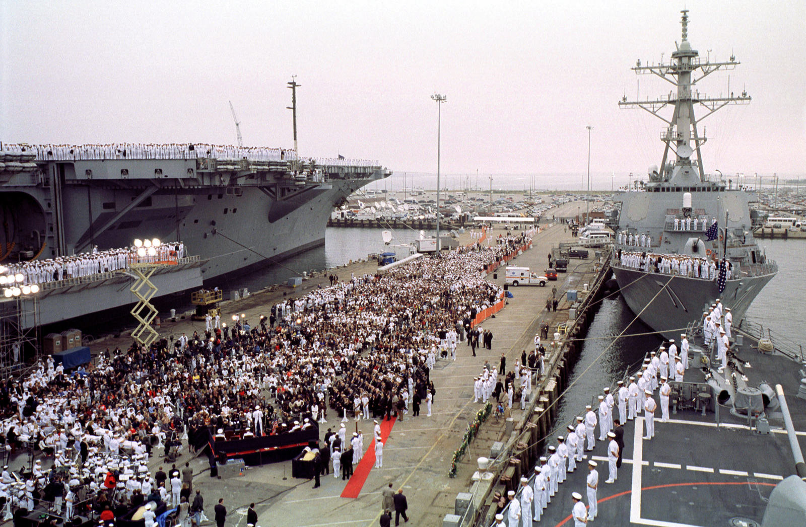 Flanked by the USS DWIGHT D. EISENHOWER (CVN 69), left and the USS ROSS (DDG 71), President Clinton and other military leaders address the families and friends of the sailors killed or missing as a result of the attack on the USS COLE (DDG 67)