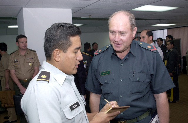 "Major Tomas Oliva, US Army South, Administration Officer, left, notes information from Major Ramon Martinez, Paraguay Armed Forces, during a ""Peace Keeping Operations South 2001 Conference."""