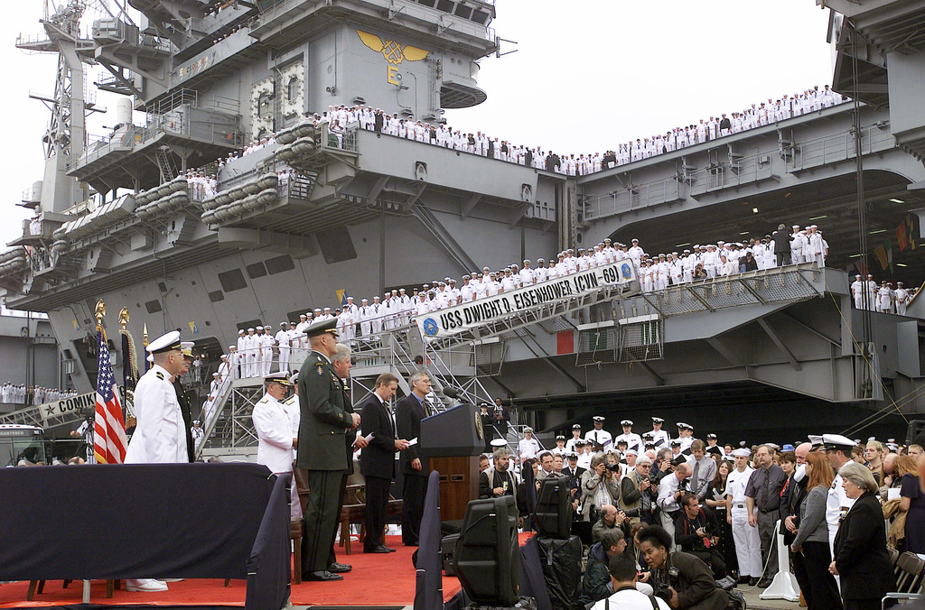 With the USS DWIGHT D. EISENHOWER (CVN 69) as a backdrop, President Clinton (Commander in CHIEF) and other military leaders address a closed memorial service for families and friends of the sailors killed and those still missing as a result of the terrorist attack on the USS COLE (DDG 67) in the port of Aden, Yemen