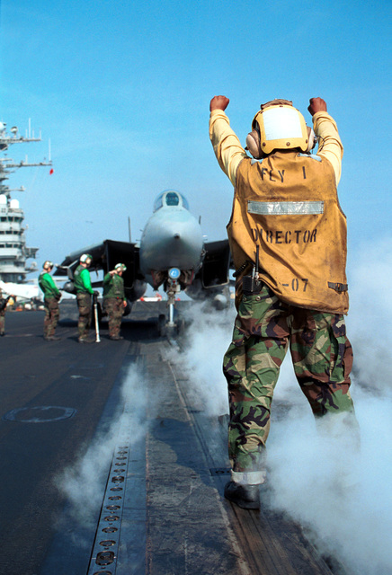 """Aviation Boatswain's Mate 3rd Class (AB3) Marissa Gibson directs an F-14 """"Tomcat"""" from the """"Jolly Rogers"""" of Fighter Squadron One Zero Three (VF-103) onto the catapult on the flight deck of the USS GEORGE WASHINGTON (CVN 73)"""