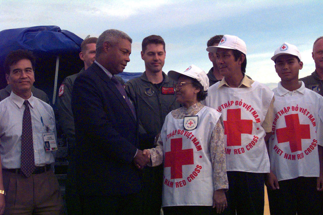 Dr. Nguyen Thi Hoi Vice President (Right shaking hands), of the Viet Nam Red Cross, accepts a water purification system from Mr. Charles A. Ray (Left shaking hands), Consul General of the United States of America at Tan Son Nhat, Viet Nam, as (Left to right behind Ray) US Air Force Captain Barry Barnes , STAFF Sergeant David Bivens and MASTER Sergeant Robert Parris, of the 517th Airlift Squadron, Elemendorf Air Force Base, Alaska, look on. (sub-standard)