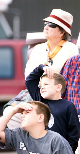 Kyle Owings, 10, (front), along with his brother Connor, 6, watch the sky along with Gwynn Burch, 80, during the USAF Thunderbirds performance (not shown) at Shaw Air Force Base, South Carolina. The Thunderbirds performed for a crowd that included special needs individuals and a large number of retirees