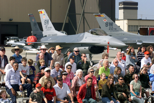 Spectators sit on bleachers in front of a display of F-16 Fighting Falcon aircraft assigned to Shaw Air Force Base, South Carolina, during the USAF Thunderbirds performance (not shown) at Shaw Air Force Base, South Carolina. The Thunderbirds performed for a crowd that included special needs individuals and a large number of retirees