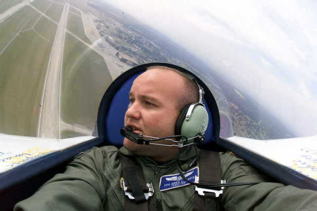 US Air Force SENIOR AIRMAN Greg L. Davis, a US Air Force photojournalist, takes a picture of himself while flying in the back seat of a Long EZ aircraft at Shawfest 2000, Shaw Air Force Base, South Carolina. The Long EZ aircraft, flown by Lon B. Anderson of Utah, performed aerobatics in front of thousands at Shaw. There isn't a traditional tail visible behind Davis' head as the aircraft has two winglet type control surfaces at the tips of the main wing