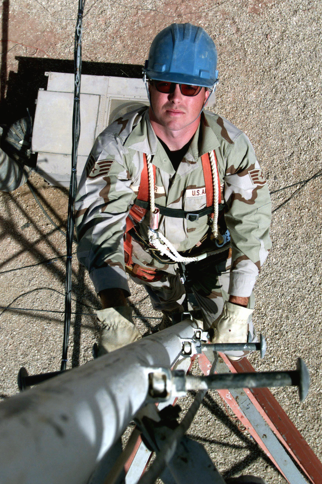 US Air Force STAFF Sergeant David Miller, a Cable/Antenna systems technician from the 341st Communications Squadron, Malmstrom Air Force Base, Montana, climbs up a communications tower to perform maintenance on a cable at Prince Sultan Air Base, Saudi Arabia, during Operation SOUTHERN WATCH. SSGT Miller is part of the coalition forces of the 363rd Air Expeditionary Wing, Prince Sultan Air Base, Saudi Arabia, that enforce the no-fly and no-drive zone in Southern Iraq to protect and defend against Iraqi aggression in support of Operation SOUTHERN WATCH