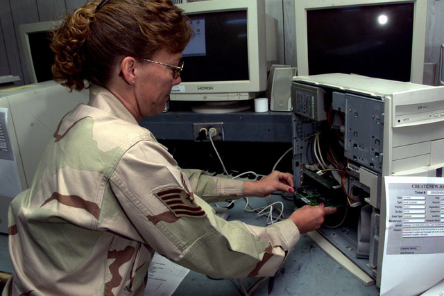 US Air Force Technical Sergeant Ramona Wolfe, the Non-Commissioned Officer in charge (NCOIC) of small computer maintenance from the 5th Combat Communications Squadron, Robbins Air Force Base, Georgia, replaces a board into a computer at Prince Sultan Air Base, Saudi Arabia, during Operation SOUTHERN WATCH. A1C Ashe is part of the coalition forces of the 363rd Air Expeditionary Wing, Prince Sultan Air Base, Saudi Arabia, that enforce the no-fly and no-drive zone in Southern Iraq to protect and defend against Iraqi aggression in support of Operation SOUTHERN WATCH