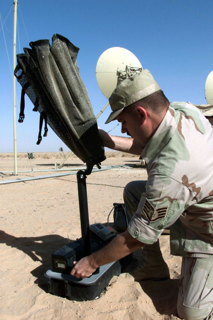 US Army STAFF Sergeant George Platzer, a Satellite Wide Band Communications Journeyman from the 54th Combat Communications Squadron, Robbins Air Force Base, Georgia, sets up an INMARSAT Satellite at Prince Sultan Air Base, Saudi Arabia, during Operation SOUTHERN WATCH. SSGT Platzer is part of the coalition forces of the 363rd Air Expeditionary Wing, Prince Sultan Air Base, Saudi Arabia, that enforce the no-fly and no-drive zone in Southern Iraq to protect and defend against Iraqi aggression in support of Operation SOUTHERN WATCH