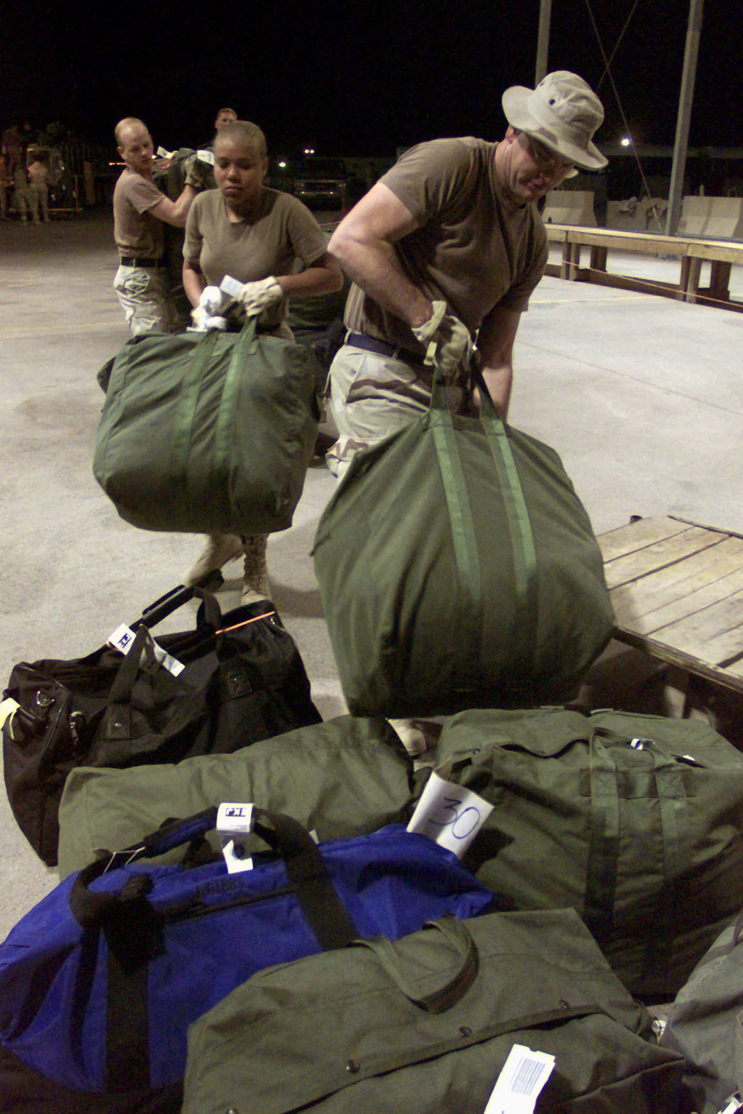 US Air Force personnel of the 363rd Expeditionary Wing, Prince Sultan Air Base, Saudi Arabia, place the bags of personnel who just came in on a Boeing 757 aircraft (Not shown). They are a part of the coalition forces of the 363rd Air Expeditionary Wing that enforces the no-fly and no-drive zone in Southern Iraq to protect and defend against Iraqi aggression. This mission is in direct support of Operation SOUTHERN WATCH