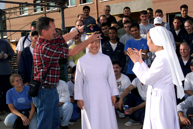 """A sister of the The Handmaids of the Sacred Heart of Jesus laughingly bends her uniform regulations as US Navy Lieutenant Commander S. Douglas Smith, Chaplain, Amphibious Squadron 11, presents her a USS ESSEX ball cap on October 23rd, 2000. The nuns invited the Marines and Sailors of the 31st Marine Expeditionary Unit (MEU) Special Operations Capable (SOC) and USS ESSEX Amphibious Ready Group (ARG) to help clean up tons of construction equipment and debris left behind when a construction project at the hospital was halted for lack of funds. Though many didn't know what the project was for, approximately 200 Marines and Sailors volunteered to help. """"It's being able to say we've done ..."""