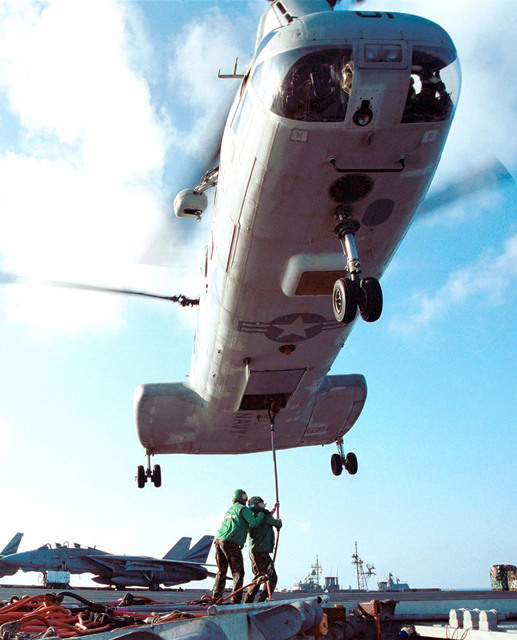 "On the USS KITTY HAWK (CV 63), Aviation Storekeeper AIRMAN (AKA) Robert Ibarra from San Antonio, Texas and Storekeeper Third Class (SK) Dasilva Leandro from Rio de Janiro, Brazil, hook empty cargo nets to a CH-46 ""Sea Knight"" helicopter during a vertical replenishment at sea (VERTREP)"