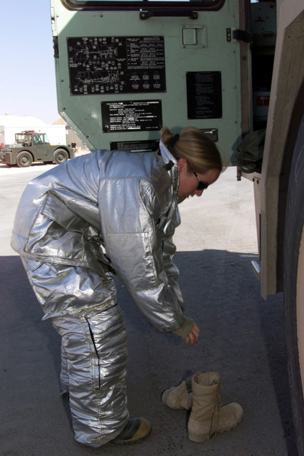US Air Force SENIOR AIRMAN Adriana D. Ofstedahl, 363rd Expeditionary Civil Engineering Squadron (ECES), Prince Sultan Air Base, Saudi Arabia, dons her protective clothing during a bunker drill. SRA Ofstedahl is part of the coalition force here to support Operation SOUTHERN WATCH, a military effort to enforce the no-fly and no-drive zone in Southern Iraq on Oct. 24, 2000