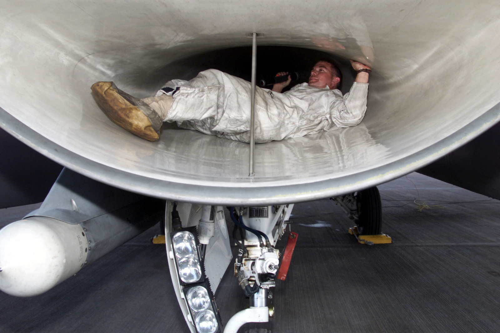 US Air Force SENIOR AIRMAN Raymond Diaz-Rios, Crew CHIEF, 22nd Expeditionary Fighter Squadron (EFS), Spangdahlem Air Base, Germany, inspects the engine of an F-16 Fighting Falcon aircraft as part of his post-flight procedures at Prince Sultan Air Base, Saudi Arabia. The 22nd EFS is part of the coalition force here to support Operation SOUTHERN WATCH, a military effort to enforce the no-fly and no-drive zone in Southern Iraq