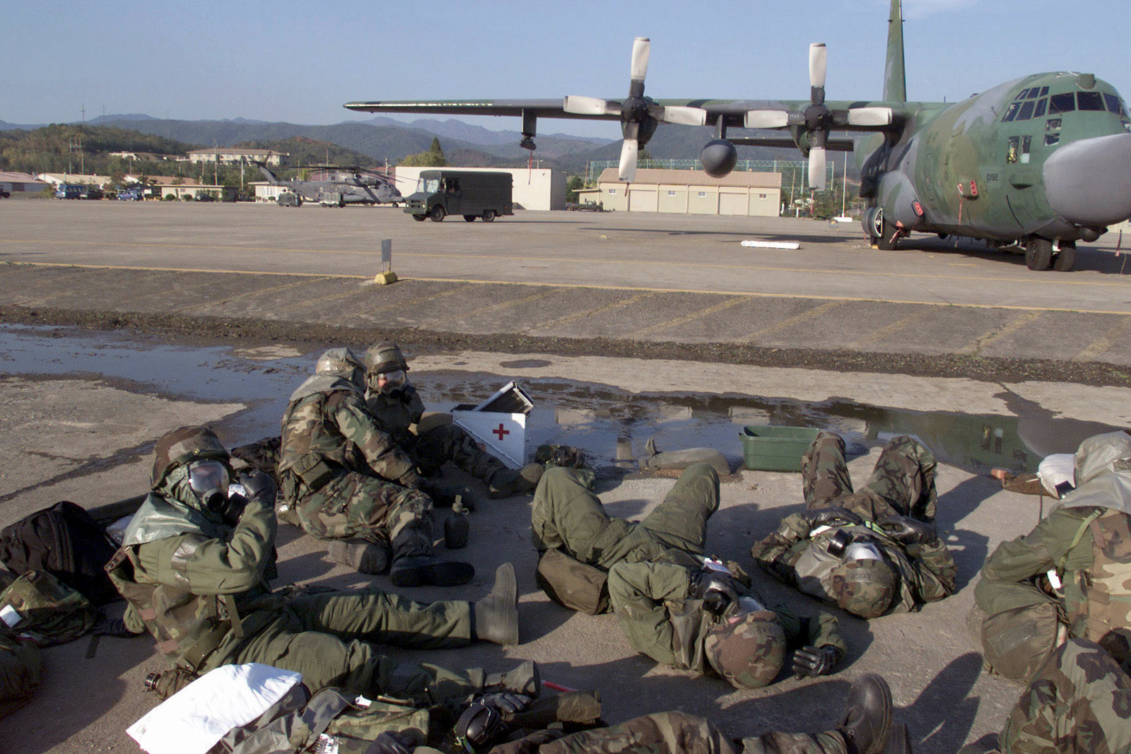Several US Air Force members of the 353rd Special Operations Group aircraft maintainers, deployed to Taegu Air Base, Korea, from Kadena Air Base, Okinawa, take cover in a simulated bunker near their MC-130H Combat Talon II aircraft during exercise FOAL EAGLE 2000 on October 26th, 2000. FOAL EAGLE is held annually in South Korea to demonstrate U.S. and South Korean military cooperation and is the U.S. Militarys largest Joint-Service, Multi-National field training drill. This year's drill involves about 25,000 active duty, Reserve, and National Guard troops from the United States and bases throughout the Pacific Command