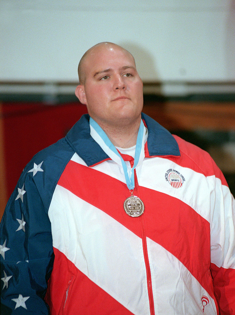 US Air Force SENIOR AIRMAN Corey Farkas, 10th Civil Engineering Squadron, Peterson Air Force Base, Colorado, stands at the podium after receiving the Silver Medal for the 130-Kg weight division at the 19th World Wrestling Championships held at Camp Lejeune Marine Corps Base, North Carolina, on October 26th, 2000. The Conseil International du Sport Militaire 19th World Military Wrestling Championship (CISM) is a multi-national wrestling tournament hosted by Lejeune, from Oct. 25-29. Competing nations include: Brazil, China, Estonia, Finland, Germany, Greece, Slovakia, Turkey, the United States, and Vietnam. Wrestlers will be competing in two different competitions, Free-Style and Greco-Roman
