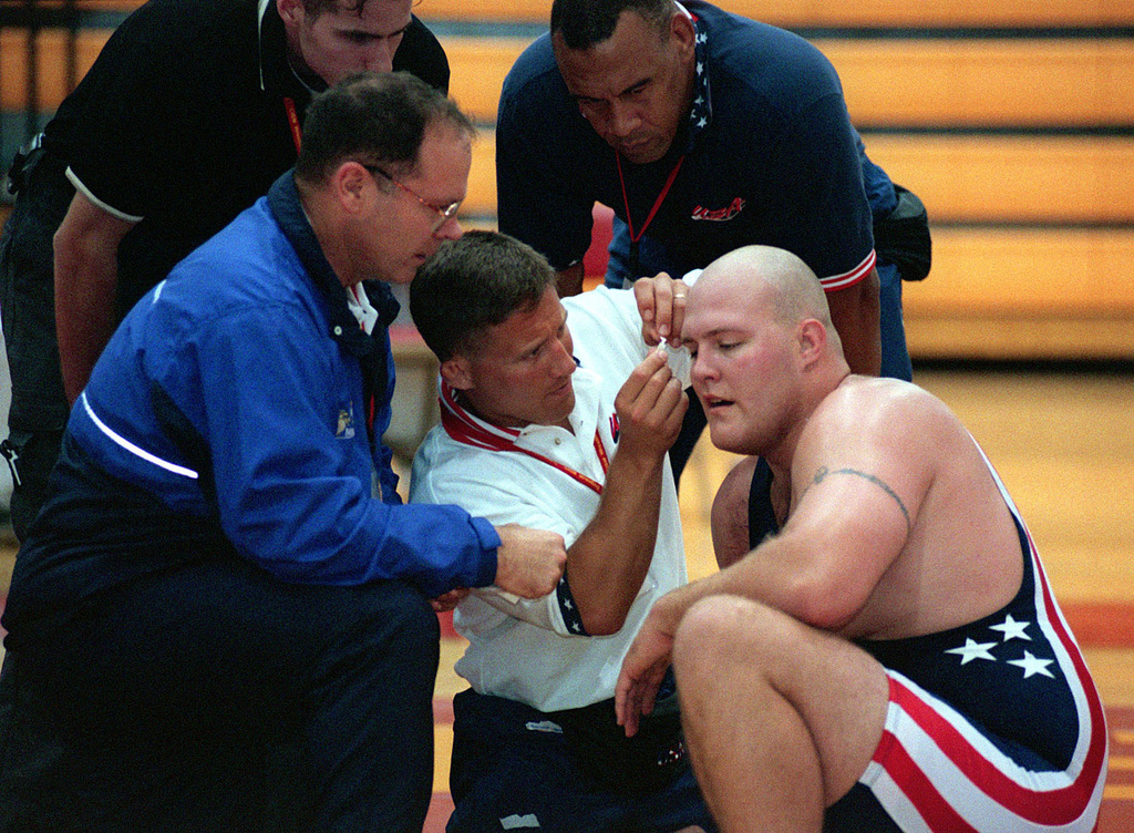 US Air Force SENIOR AIRMAN Corey Farkas, 10th Civil Engineering Squadron, Peterson Air Force Base, Colorado, receives medical treatment from All Marine Wrestling Coach, Captain Jay Antonelli, Headquarters and Service Batalion, Marine Corps Base, Quantico, Virginia, at the19th World Wrestling Championships held at Camp Lejeune Marine Corps Base, North Carolina, on October 26th, 2000. The Conseil International du Sport Militaire 19th World Military Wrestling Championship (CISM) is a multi-national wrestling tournament hosted by Camp Lejeune from Oct. 25-29. Competing nations include: Brazil, China, Estonia, Finland, Germany, Greece, Slovakia, Turkey, the United States, and Vietnam. The ...