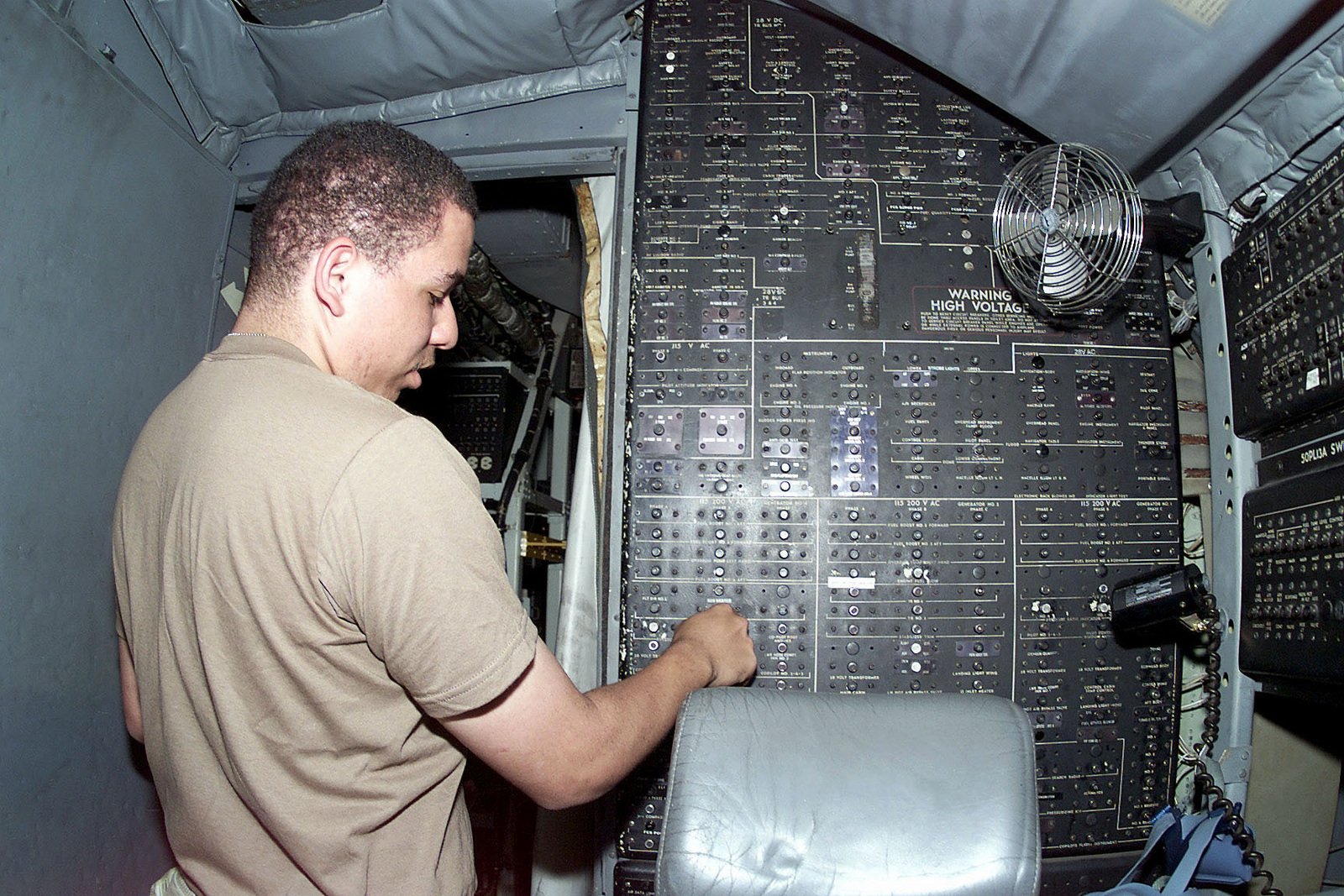US Air Force SENIOR AIRMAN John Murphy, a Crew CHIEF from the 363rd Expeditionary Reconnaissance Squadron, Prince Sultan Air Base, Saudi Arabia, performs post-flight procedures in the cockpit of a USAF RC-135 Rivet Joint Reconnaissance aircraft at the base, on October 26th, 2000. SRA Murphy is part of the coalition force here to support Operation SOUTHERN WATCH, a military effort to enforce the no-fly and no-drive zone in Southern Iraq