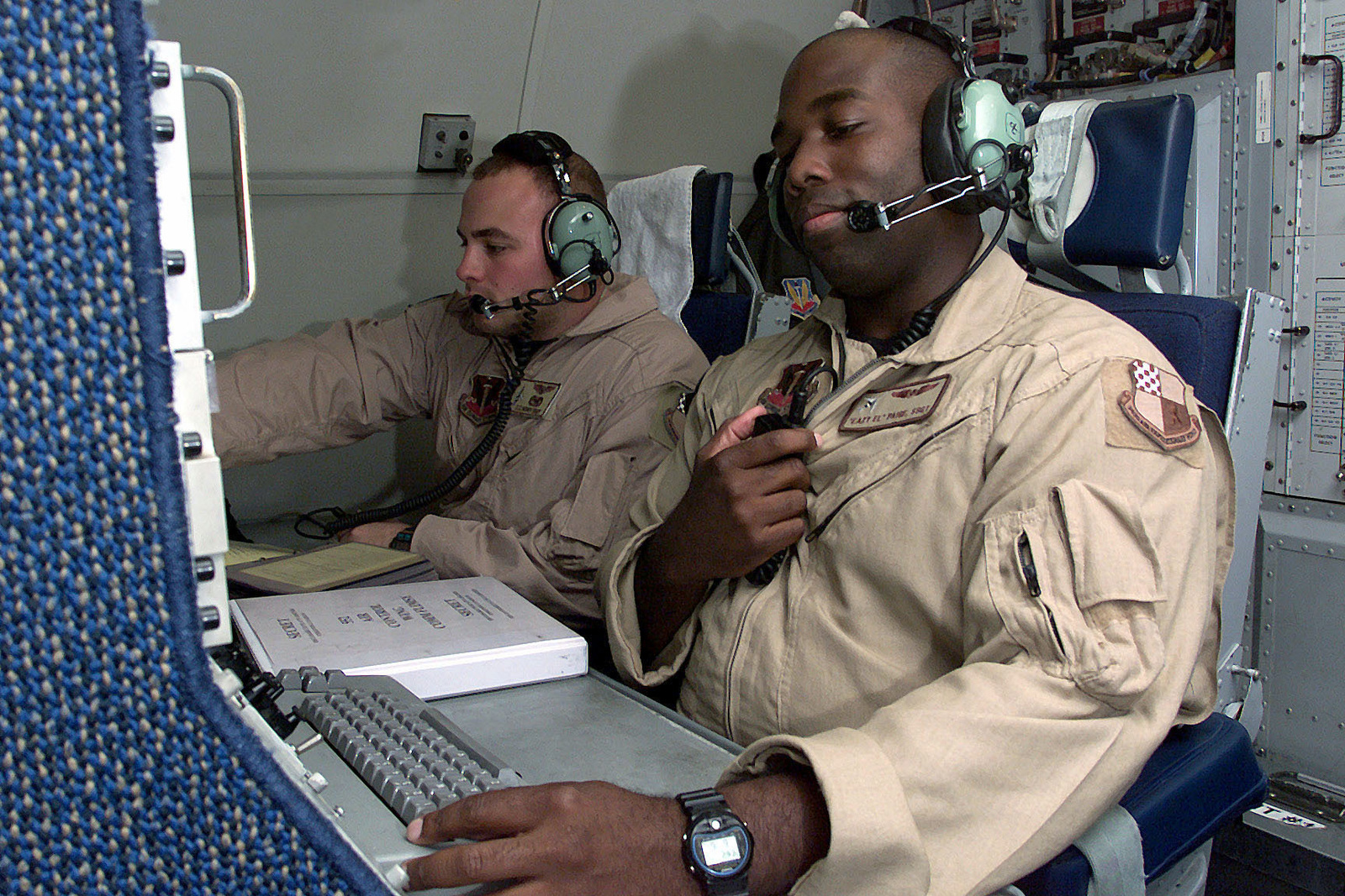 US Air Force STAFF Sergeant Elliott Paige (Foreground) a Computer Systems Operator, 964th Airborne Air Control Squadron, Tinker Air Force Base, Oklahoma, does his preflight checklist before a flight at Prince Sultan Air Base, Saudi Arabia. SSGT Harpek is a part of the coalition forces of the 363rd Air Expeditionary Wing that enforces the no-fly and no-drive zone in Southern Iraq to protect and defend against Iraqi aggression. This mission is in direct support of Operation SOUTHERN WATCH