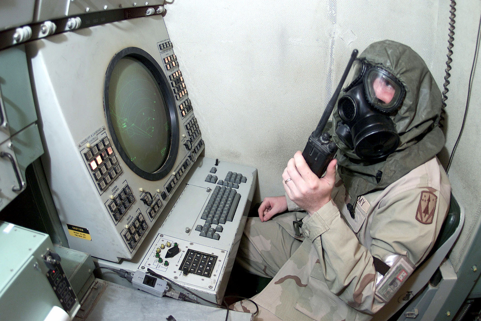 US Army Second Lieutenant Brendan E. Sullivan, Tactical Control Officer, Delta Battery Task Force, communicates with his team through his gas mask during a drill in the engagement control station for the Patriot missile system, Prince Sultan Air Base, Saudi Arabia, on October 26th, 2000. 2LT Sullivan is part of the coalition force here to support Operation SOUTHERN WATCH, a military effort to enforce the no-fly and no-drive zone in Southern Iraq