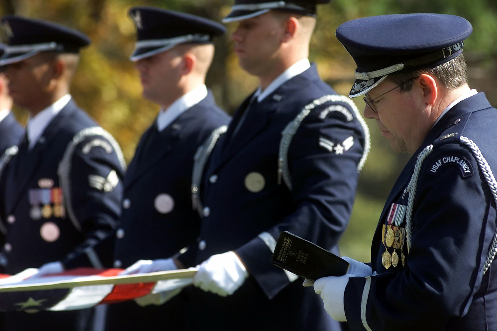 A US Air Force Chaplain reads from a book of worship as other US Air Force members hold the American flag during a full honor funeral for US Air Force Second Lieutenant Richard Vandegeer at Arlington National Cemetery on October 27, 2000