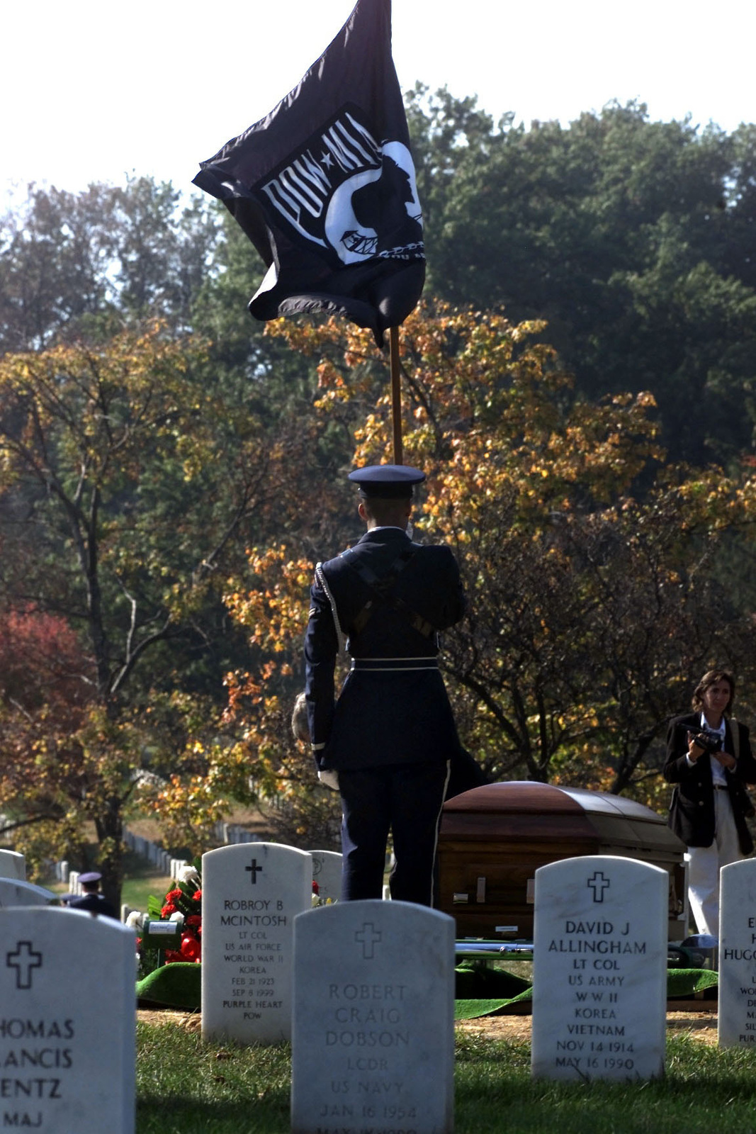A US Air Force member, with his back to the camera, holds the POW/MIA flag during a full honor funeral for US Air Force Second Lieutenant Richard Vandegeer at Arlington National Cemetery on October 27, 2000
