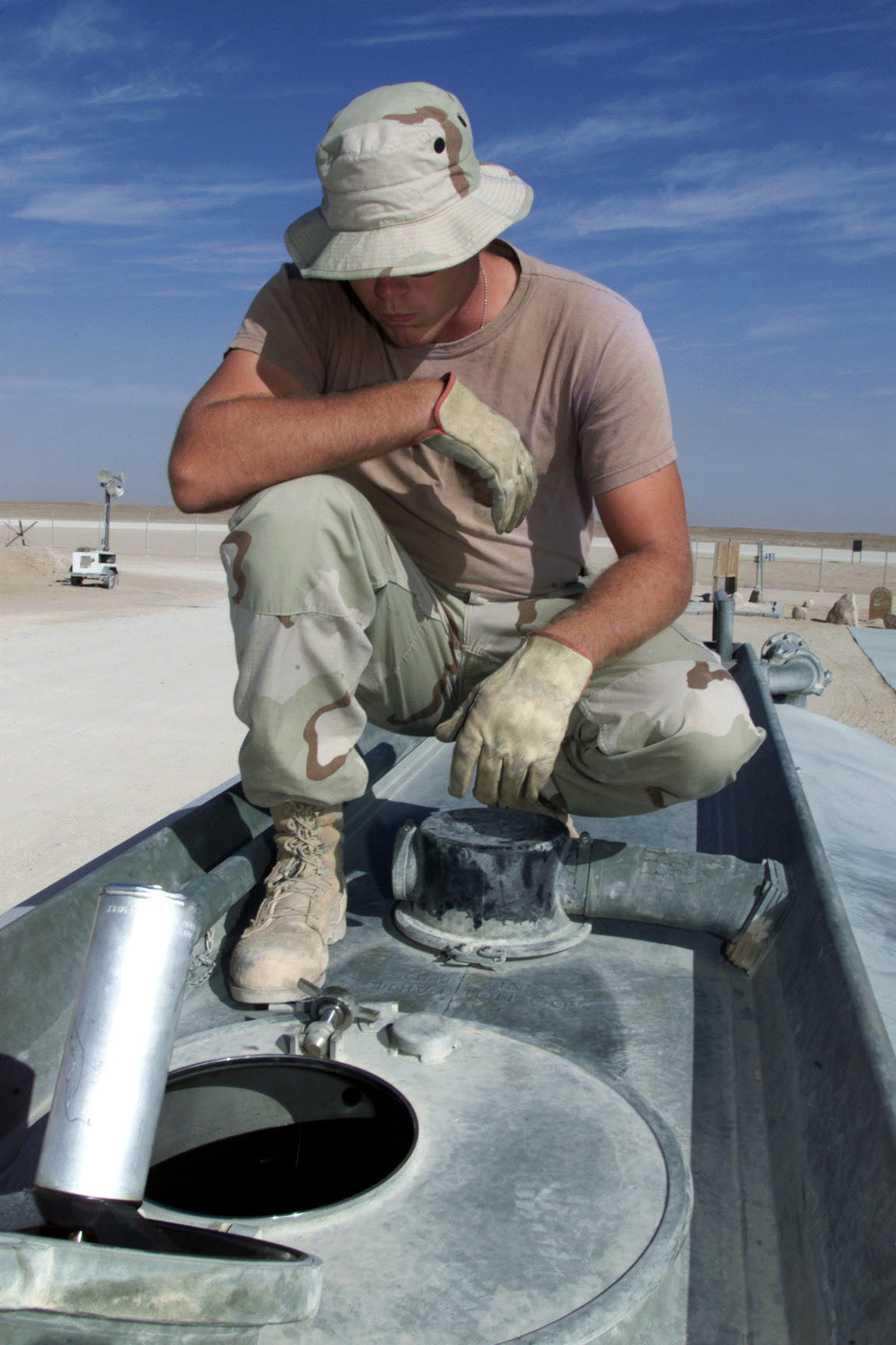 US Air Force AIRMAN First Class Billy Christy, 363rd Expeditionary Supply Squadron, Prince Sultan Air Base, Saudi Arabia, visually checks the level of fuel as it is pumped into his truck. A1C Christy is part of the coalition force here to support Operation SOUTHERN WATCH, a military effort to enforce the no-fly and no-drive zone in Southern Iraq