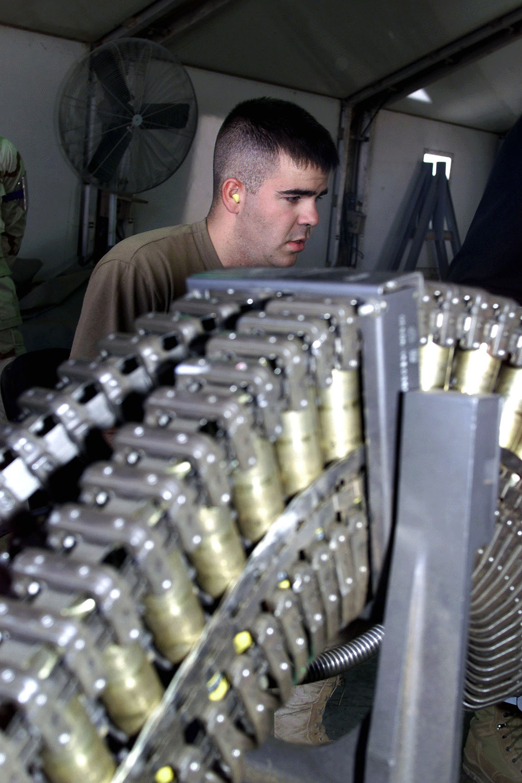 US Air Force AIRMAN First Class Lance Peak, 363rd Expeditionary Maintenance Squadron, Prince Sultan Air Base, Saudi Arabia, loads 20mm rounds into a universal ammunition loading system. A1C Peak is part of the coalition force here to support Operation SOUTHERN WATCH, a military effort to enforce the no-fly and no-drive zone in Southern Iraq