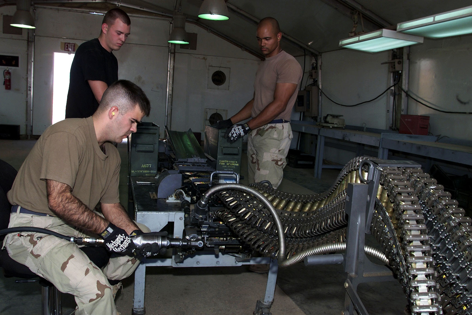 US Air Force AIRMAN First Class Lance Peak, USAF AIRMAN First Class Bradford Neumann, and USAF AIRMAN First Class Horace Bowler, 363rd Expeditionary Maintenance Squadron, Prince Sultan Air Base, Saudi Arabia, load 20mm rounds into a universal ammunition loading system. The 363rd is part of the coalition force here to support Operation SOUTHERN WATCH, a military effort to enforce the no-fly and no-drive zone in Southern Iraq