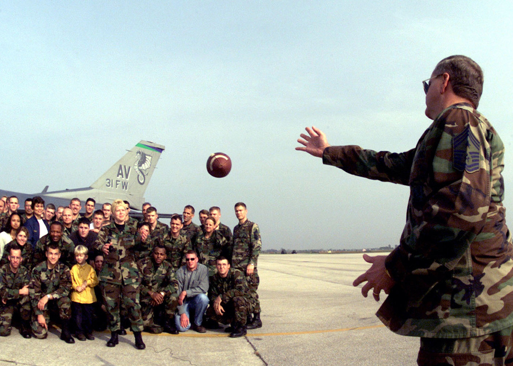 US Air Force CHIEF MASTER Sergeant Bruce Reid, the 31st Fighter Wing Command CHIEF MASTER Sergeant at Aviano Air Base, Italy, throws a pass to United States Air Force in Europe Command CHIEF MASTER Sergeant Vickie C. Mauldin during a taping for a Super Bowl commercial for Armed Forces Network. CMSGT Mauldin is surrounded by football crazed troops attending Avinao's Safety Day Block Party