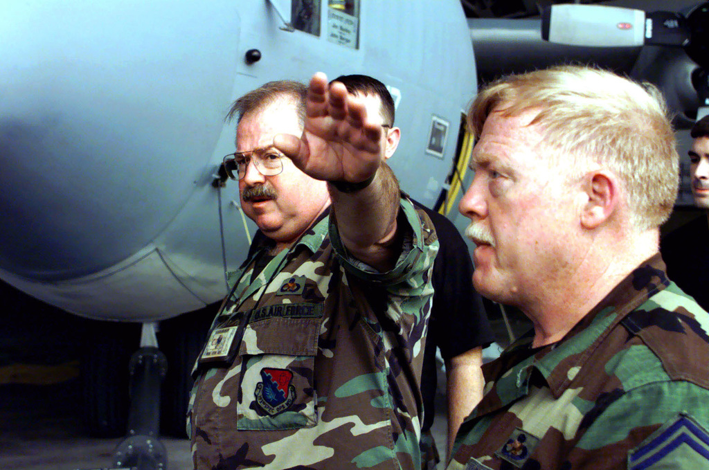 US Air Force MASTER Sergeant Ronald Keeney (left) and US Air Force SENIOR MASTER Sergeant Lowell Wise give instructions to their crew prior to towing operation to move an EC130E Hercules aircraft (not shown) out of its hangar. MSGT Keeney and MSGT Wise are with the 193rd Special Operations Wing, Pennsylvania Air National Guard, deployed to Kadena Air Base, Japan, in support of the units' participation in Operation FOAL EAGLE 2000