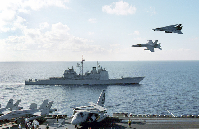 """An F-14 """"Tomcat"""" from the Fighter Squadron One Zero Three (VF 103) """"Jolly Rogers"""" and an F/A-18 Hornet from the Fighter Attack Squadron Three Four (VFA 34) Blue Blasters pass between the guided missile cruiser USS NORMANDY (CG 60) and the USS GEORGE WASHINGTON (CVN 73) at near supersonic speed"""