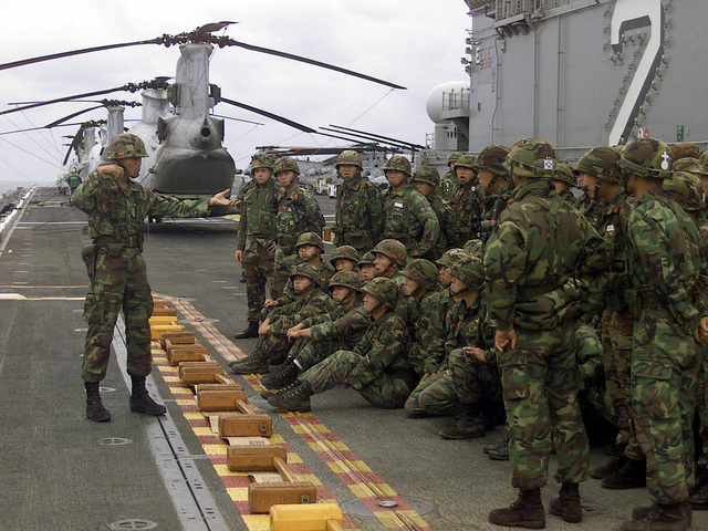 Republic of Korea (ROK) Marines receive a safety brief and instructions in preparation for a live-fire weapons shoot on the flight deck of USS ESSEX (LHD 2). The ROK Marines fired US Marine Colt M16A2 5.56mm Rifles as part of the bilateral information exchange made possible by the ESSEX's hosting approximately 100 ROK Marines for nearly a week. Marines from the 31st Marine Expeditionary Unit (MEU) Special Operations Capable (SOC) trained with the ROK Marines, exchanging close-combat skills, conducting a combined amphibious raid, and other training exercises as part of Exercise FOAL EAGLE 2000. FOAL EAGLE is a combined arms exercise conducted between Korean and the US forces
