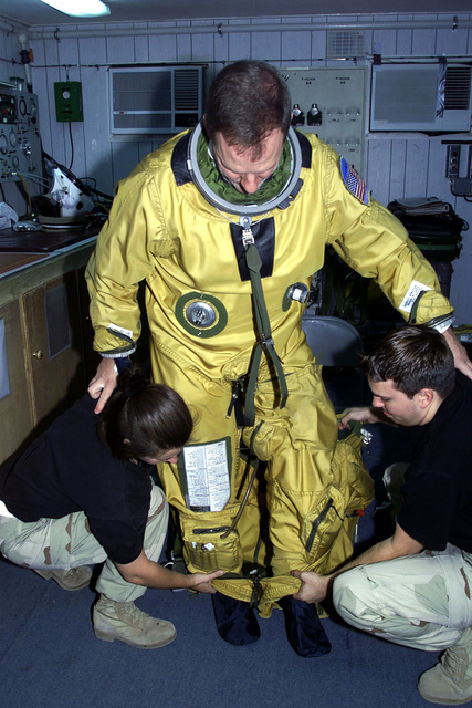 US Air Force Captain Darrell Dunn, a U-2 pilot for 363rd Expeditionary Reconnaissance Squadron, Prince Sultan Air Base, Saudi Arabia, gets suited up before his flight with the help of USAF SENIOR AIRMAN Cindy Nakoski and USAF SENIOR AIRMAN John Harry, physiology support. CPT Dunn, SRA Nakoski, and SRA Harry are part of the coalition force here to support Operation SOUTHERN WATCH, a military effort to enforce the no-fly and no-drive zone in Southern Iraq