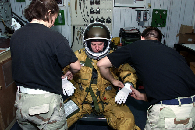 US Air Force Captain Darrell Dunn, U-2 pilot, 363rd Expeditionary Reconnaissance Squadron, Prince Sultan Air Base, Saudi Arabia, gets suited up before his flight with the help of USAF SENIOR Airmen Cindy Nakoski and USAF SENIOR AIRMAN John Harry, of physiology support. CPT Dunn, SRA Nakoski, and SRA Harry are part of the coalition force here to support Operation Southern Watch, a military effort to enforce the no-fly and no-drive zone in Southern Iraq